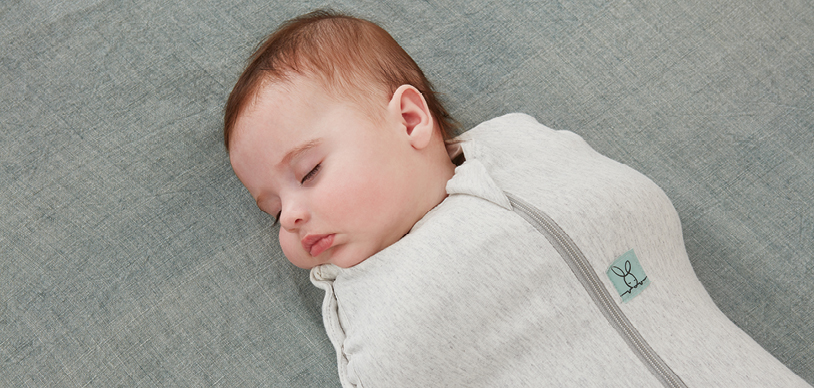 Newborn baby sleeping restfully on back, wearing a swaddle pouch
